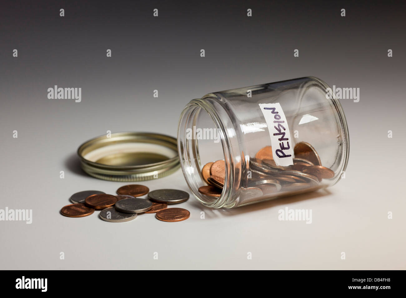 Spilled glass jar of coins saved for pension - USA - Stock Image