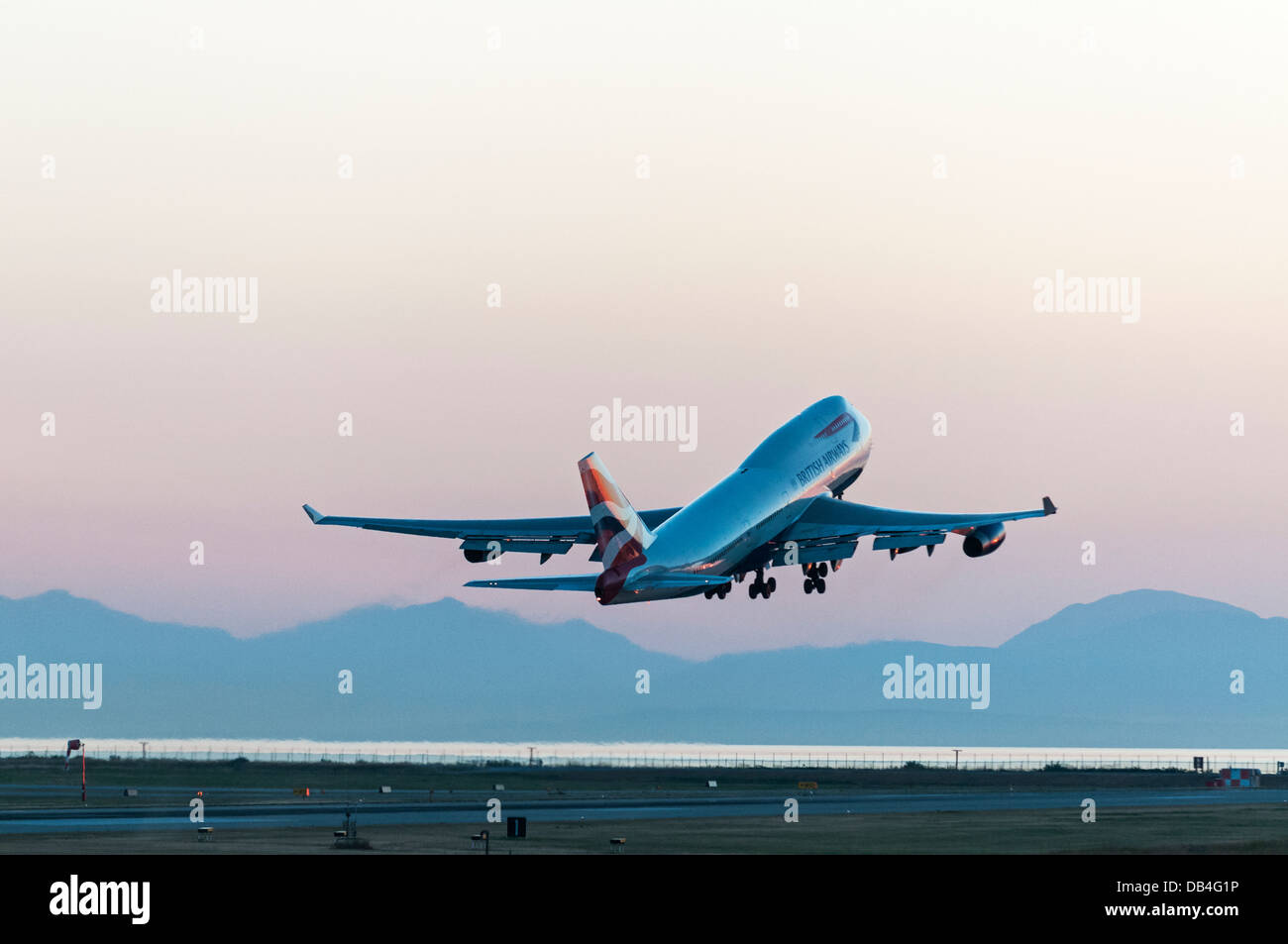 A British Airways (BA) Boeing 747-400 (747-436) wide body jumbo jet airliner takes off at dusk from Vancouver International, Stock Photo