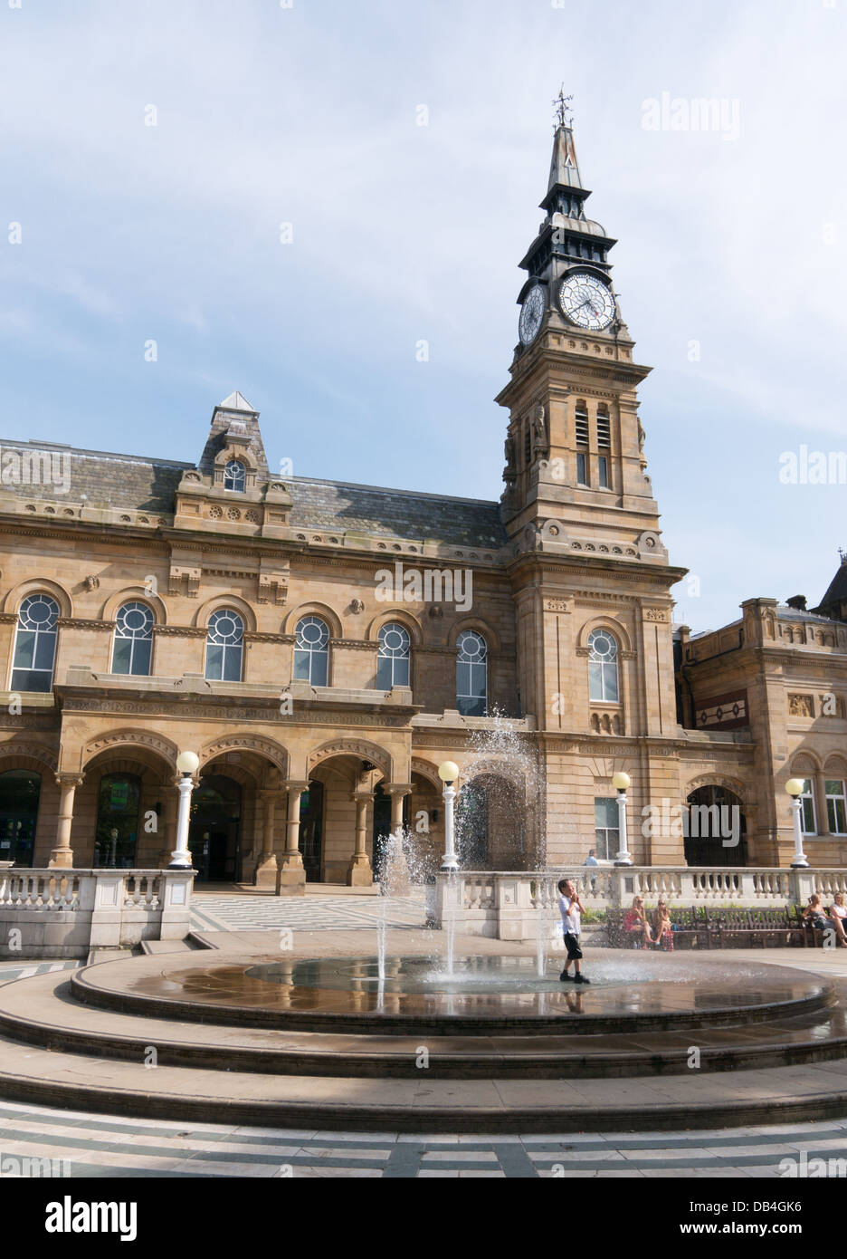 Young boy cools off in fountain in front of Southport town hall during summer heatwave, north west England, UK - Stock Image