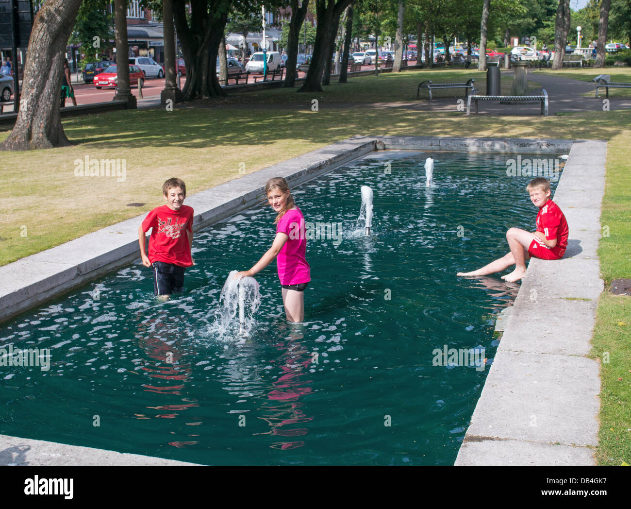 Children cool off in water feature in Southport park during summer heatwave, north west England, UK - Stock Image
