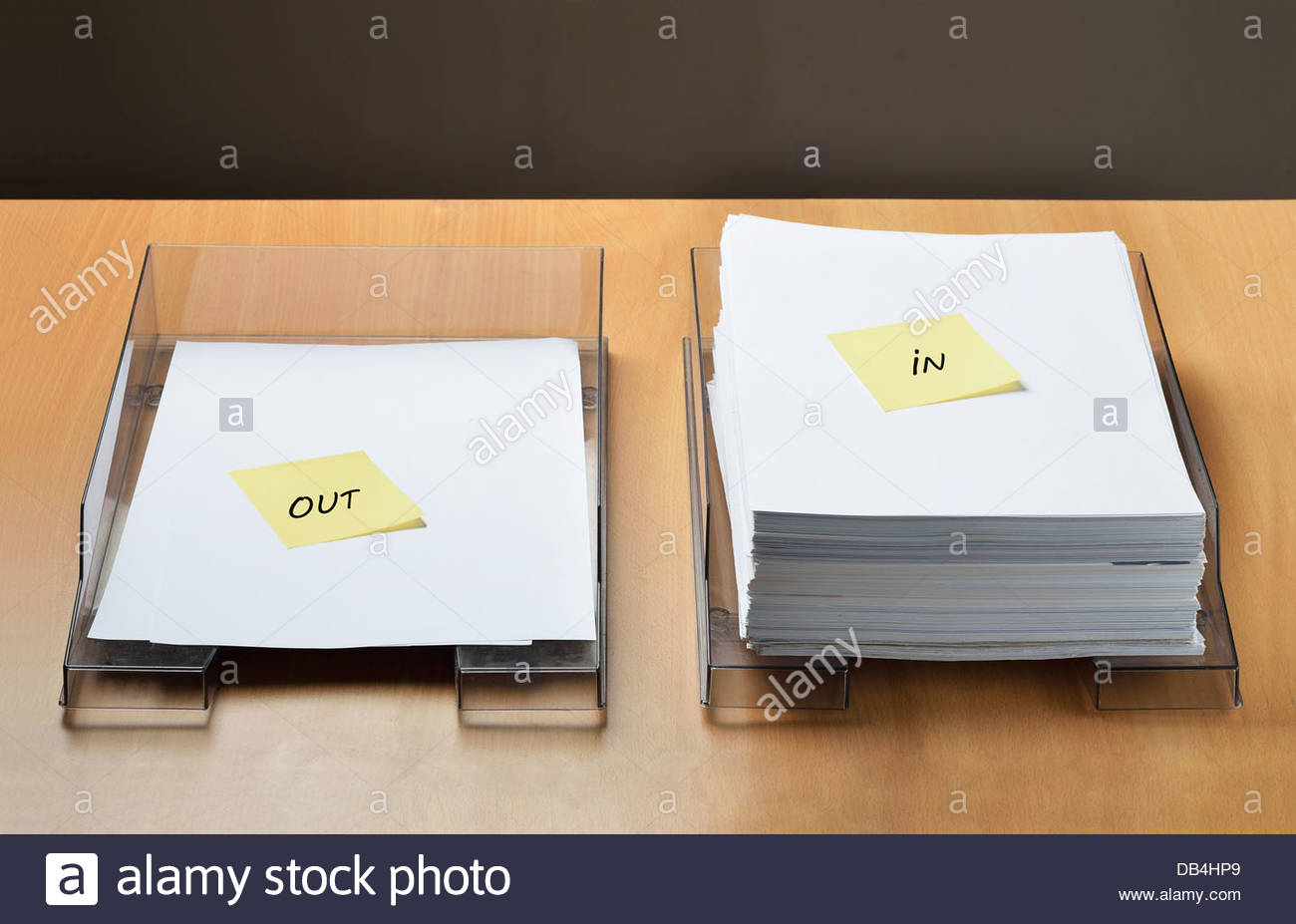 Two paper trays, one empty for the work already done and one full for the work to do - Stock Image