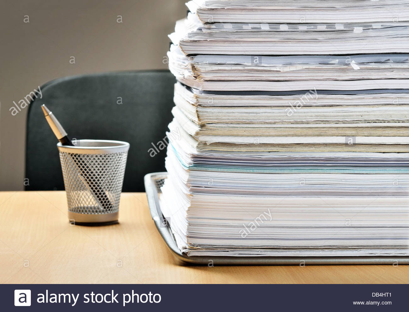 A huge pile of paperwork on a desk - Stock Image