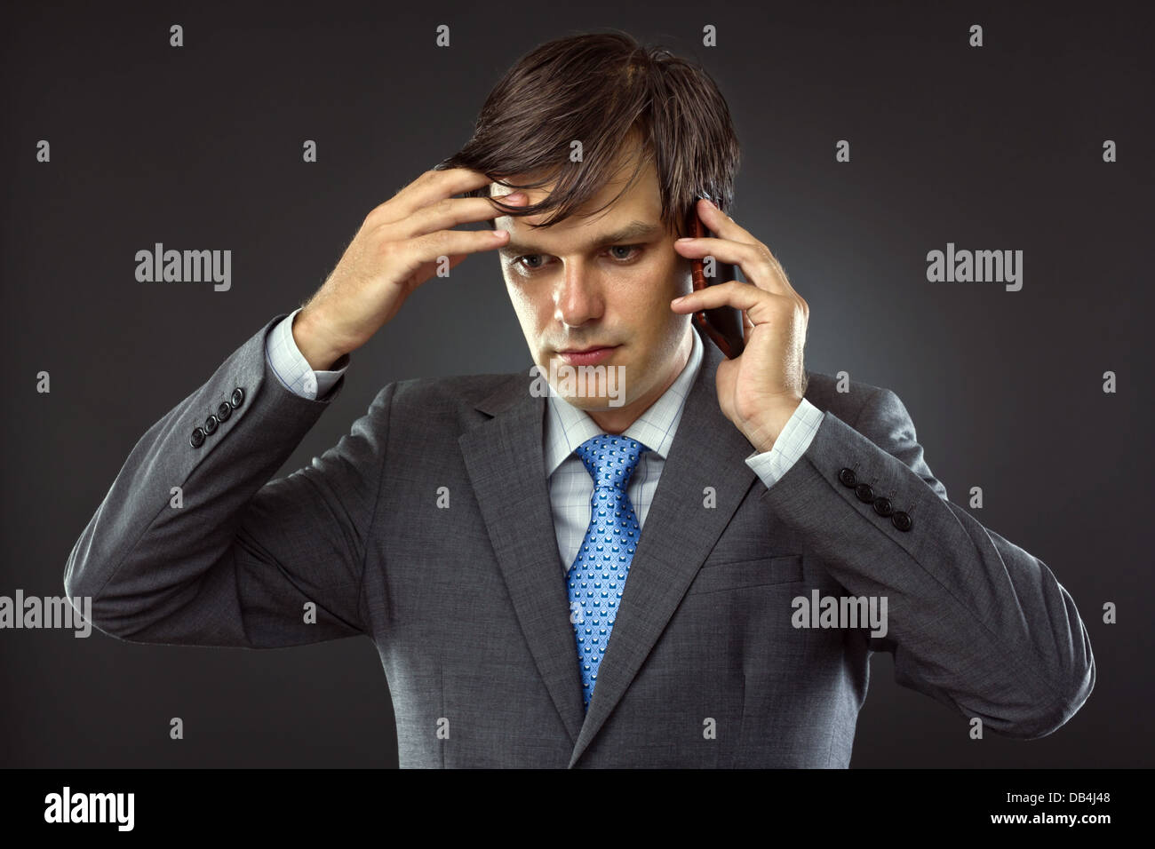 Business man talking on his cellphone and thinking - Stock Image
