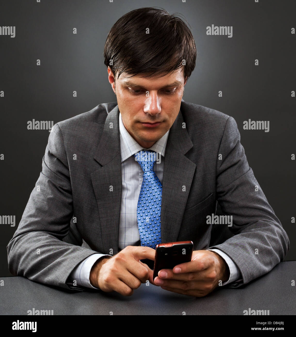 Young businessman sitting behind his desk looking at his mobile phone on gray - Stock Image