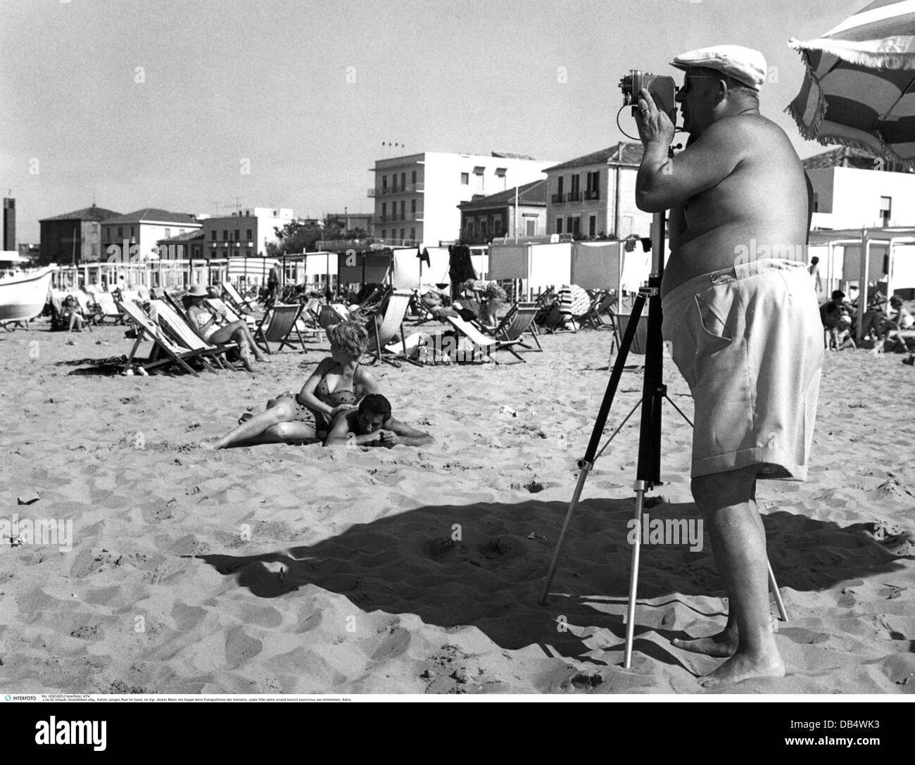 tourism, beach life, thick man with cap taking a picture of a couple lying in the sand, late 1950s, , Additional - Stock Image