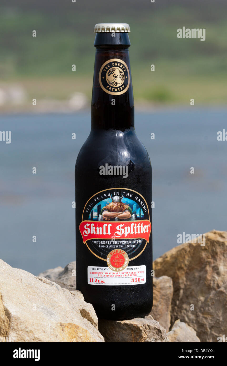 A bottle of the Orkney Brewery's Skull Splitter Rich Ale, in front of the Bay of Firth, Mainland, Orkney. - Stock Image