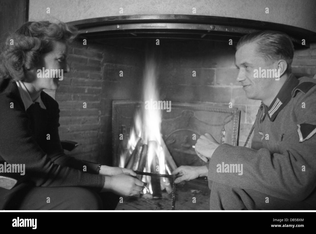 events, Second World War / WWII, Germany, Wehrmacht soldier with a woman in front of a fireplace, circa 1941, Additional - Stock Image