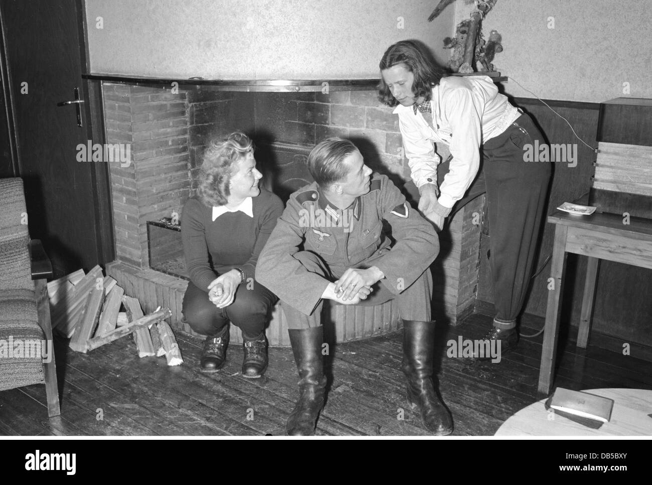events, Second World War / WWII, Germany, Wehrmacht soldier with two women in front of a fireplace, circa 1941, - Stock Image