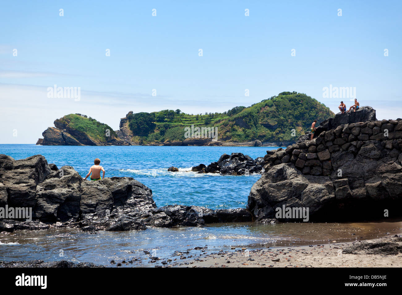 Boys playing on the rocks opposite to the islet of Vila Franca off São Miguel coast. - Stock Image