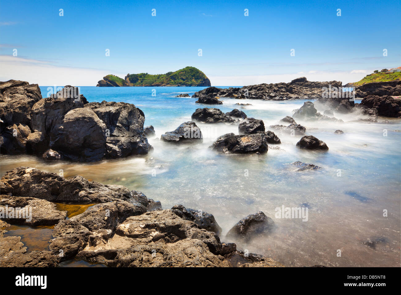 View from the rocky coast of São Miguel to the islet of Vila Franca. Long exposure shot. - Stock Image