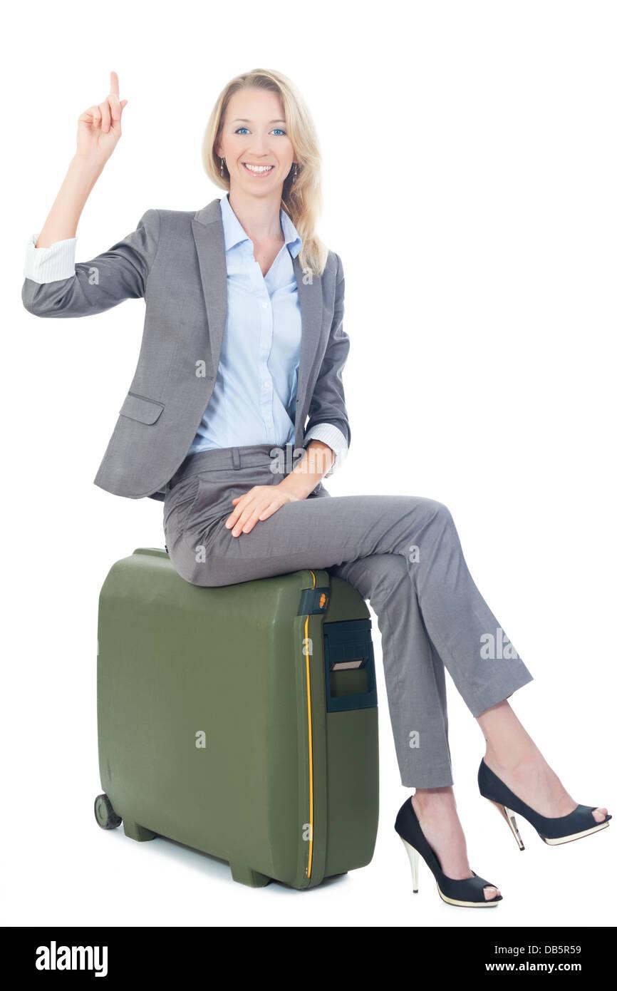 businessfrau sitzt auf koffer - Stock Image