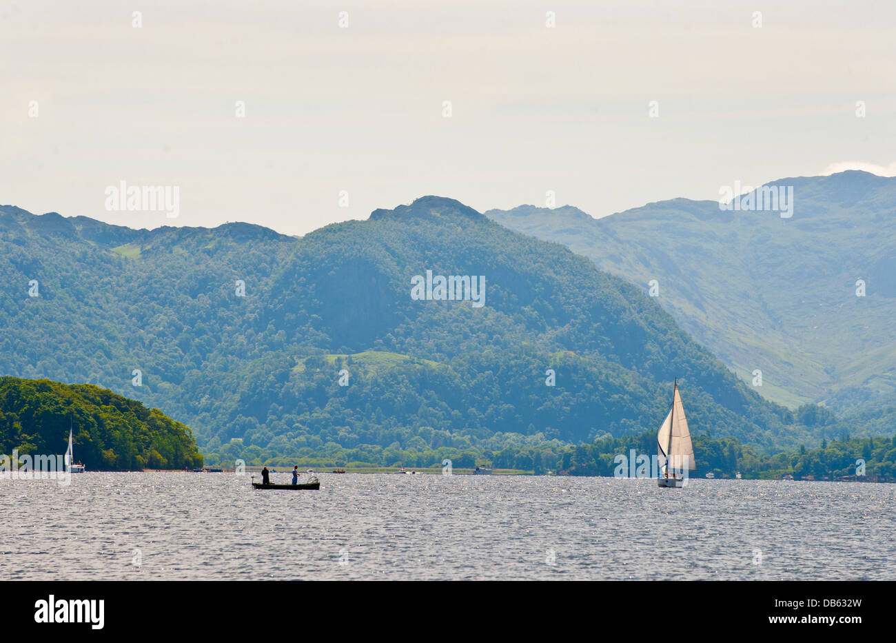 Fishermen in a boat and a yacht sailing on Lake Derwentwater in Keswick in the Lake District. - Stock Image