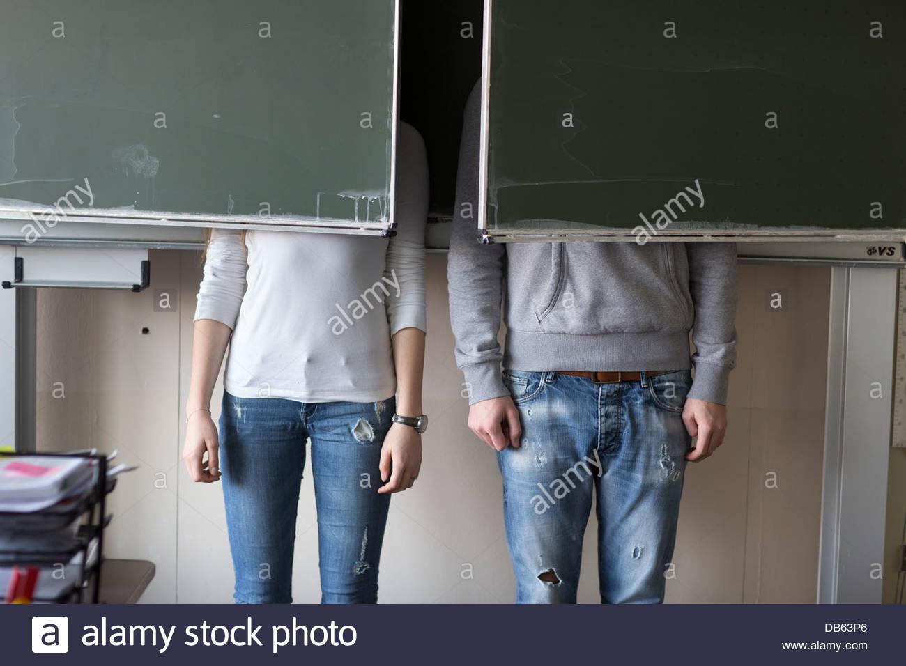 Students hiding behind blackboards - Stock Image