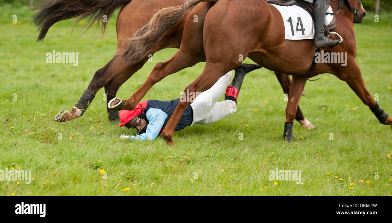 Jockey being dragged along by a horse during a race Stock Photo