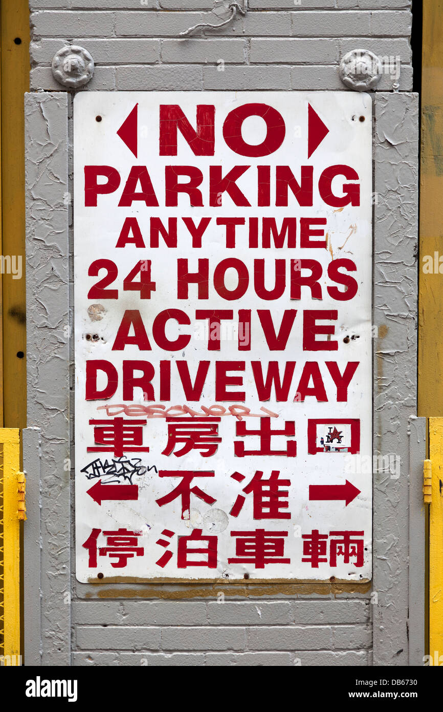 No parking sign in English and Chinese language in New York City - Stock Image