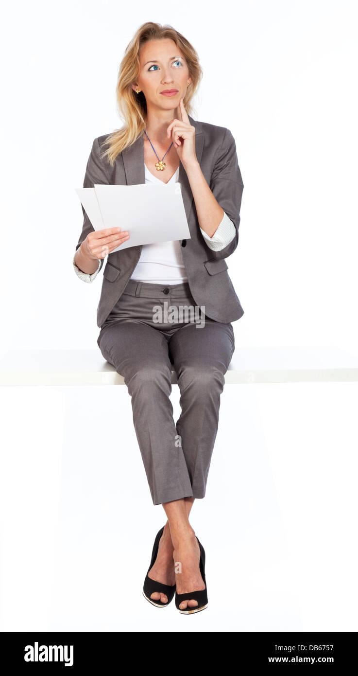 Frau sitzt überlegt - Stock Image
