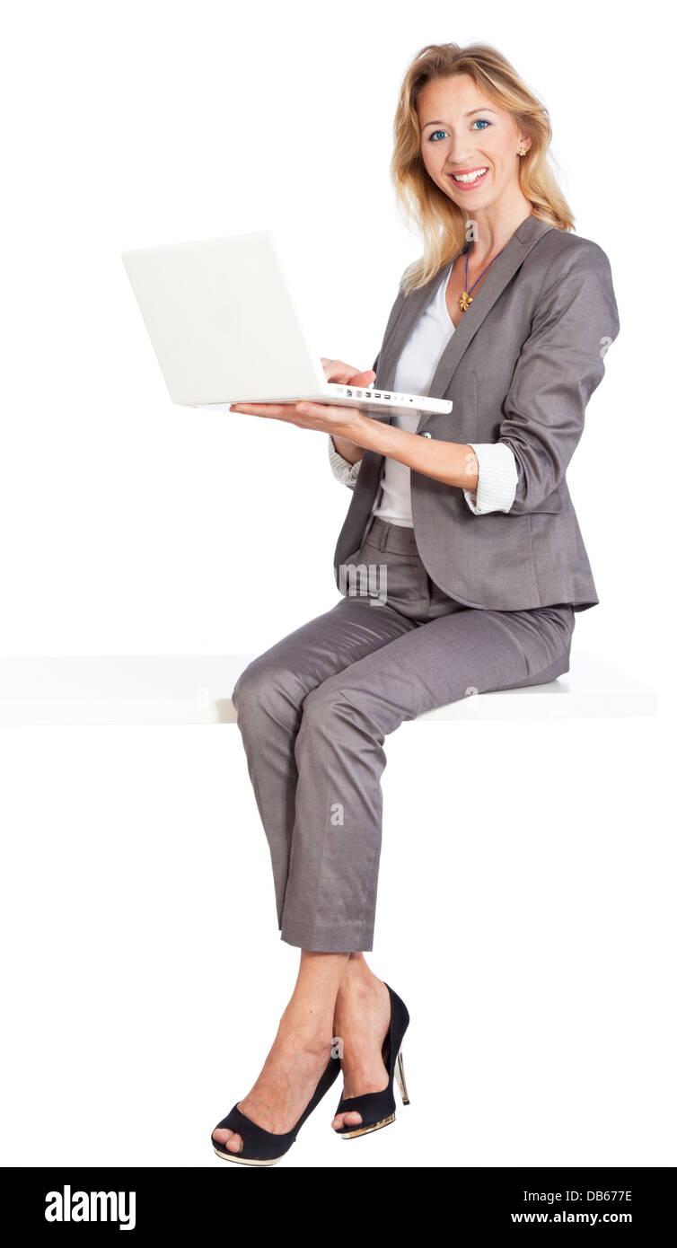Frau sitzt mit Laptop - Stock Image