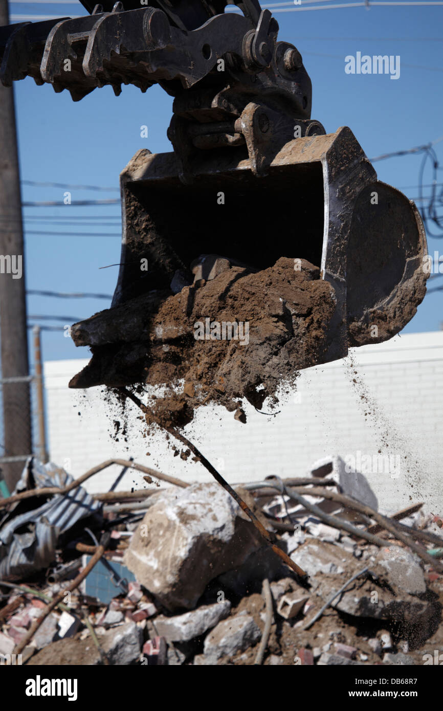 Excavator bucket dumping debris from demolition site. - Stock Image