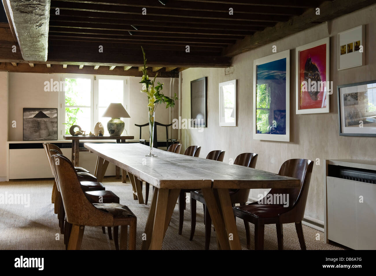 Wooden dining table and chairs under beamed ceiling in Antwerp apartment of Boris Vervoordt - Stock Image