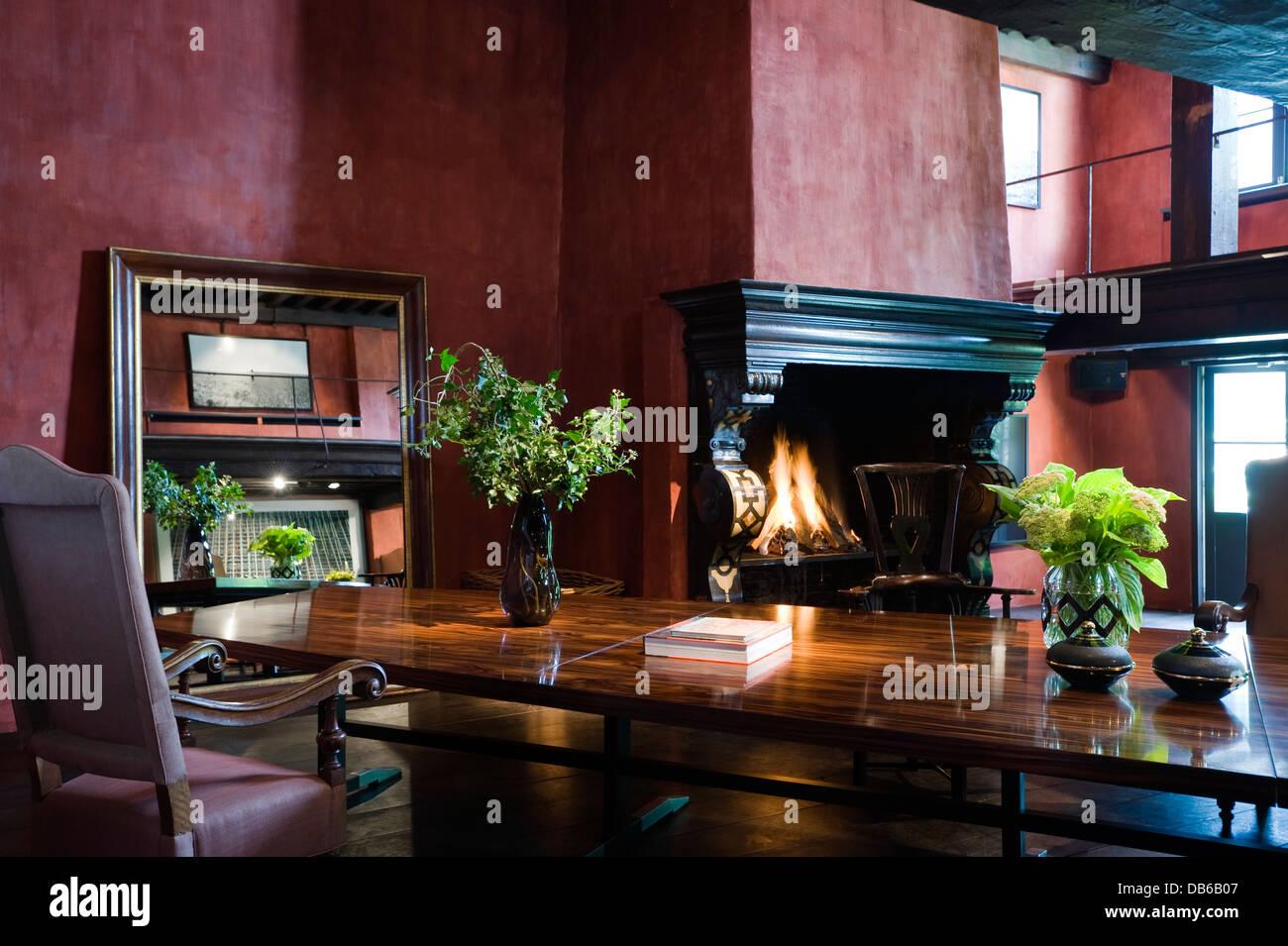 Polished wooden table with dark wood platform in Antwerp apartment of Boris Vervoordt - Stock Image