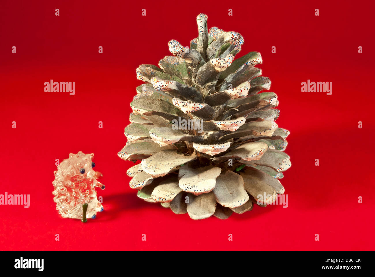 Quartz hedgehog near the fir-cones, isolated on a red background. - Stock Image