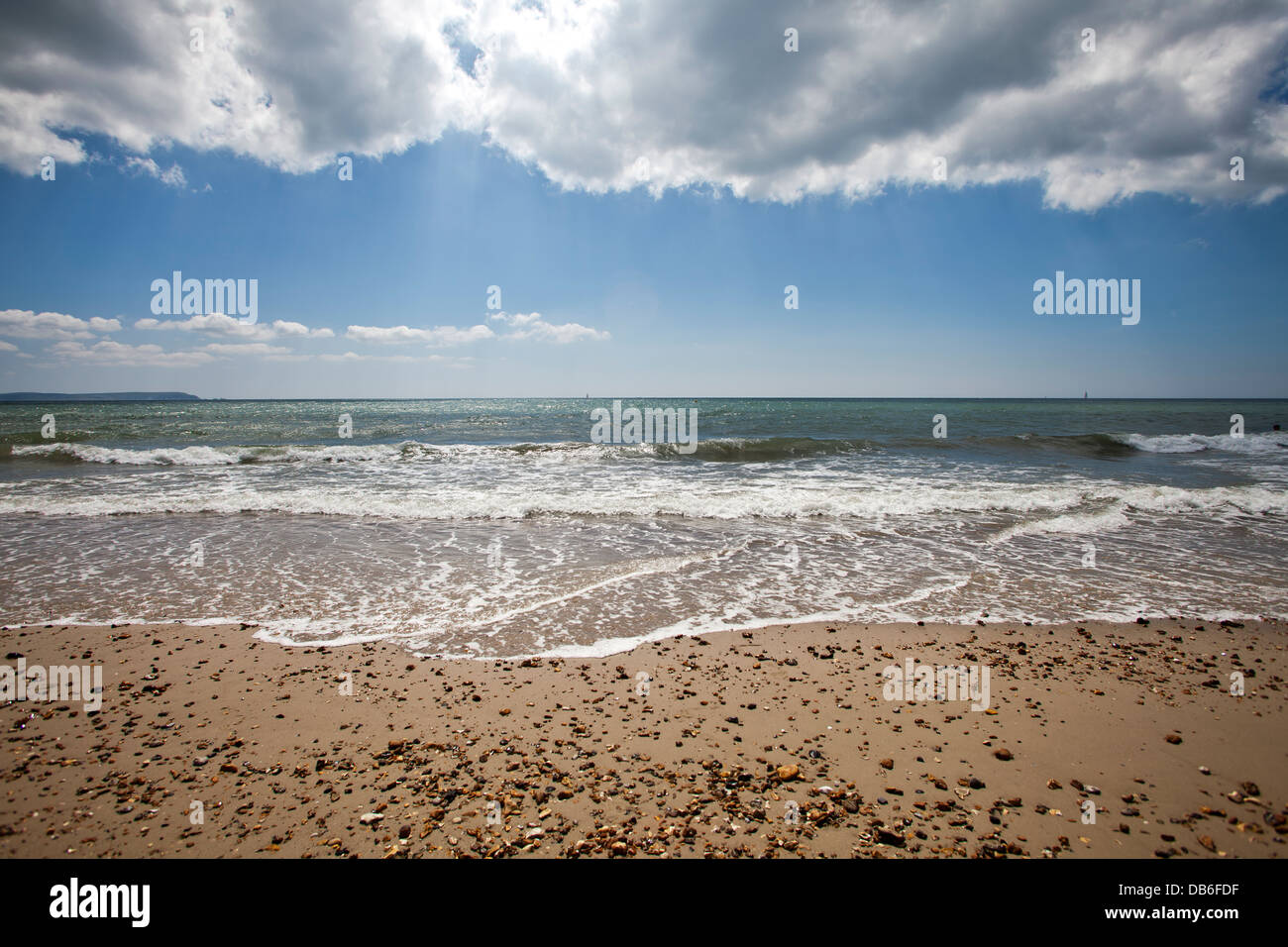 an empty strand of beach with gentle surf under sunlit clouds - Stock Image