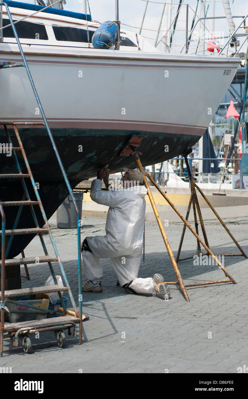 Man performing maintenance on the hull of a sailboat, Granville Island Vancouver British Columbia. - Stock Image