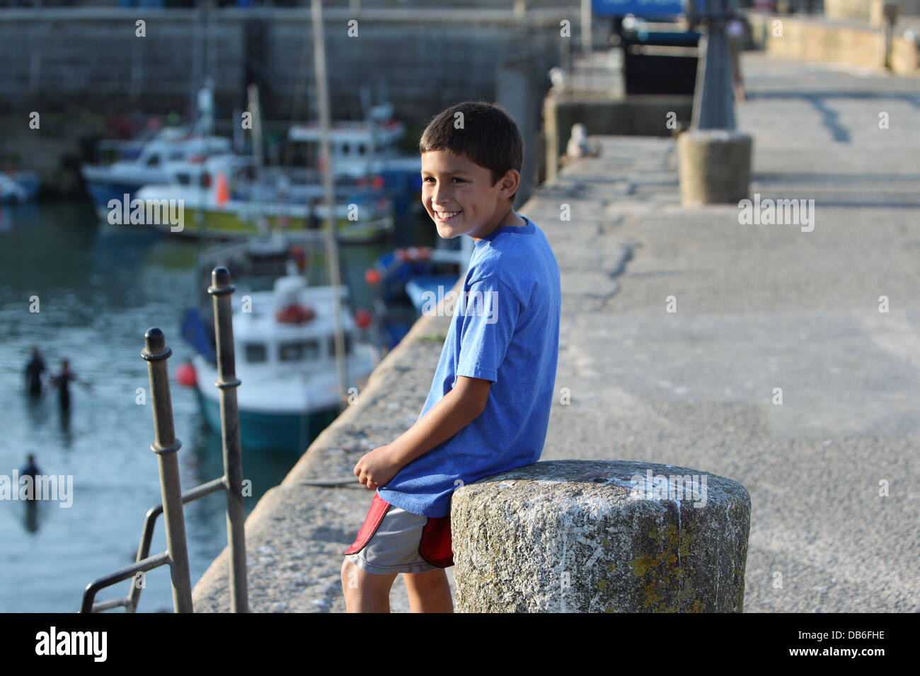 Young Hispanic boy smiles while sitting on a concrete bollard on an old harbor wall - Stock Image