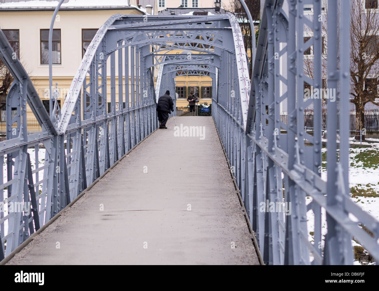 Beggar on the Mozartsteg. A traditionally dressed gentleman approaches a beggar on the Mozart Bridge - Stock Image