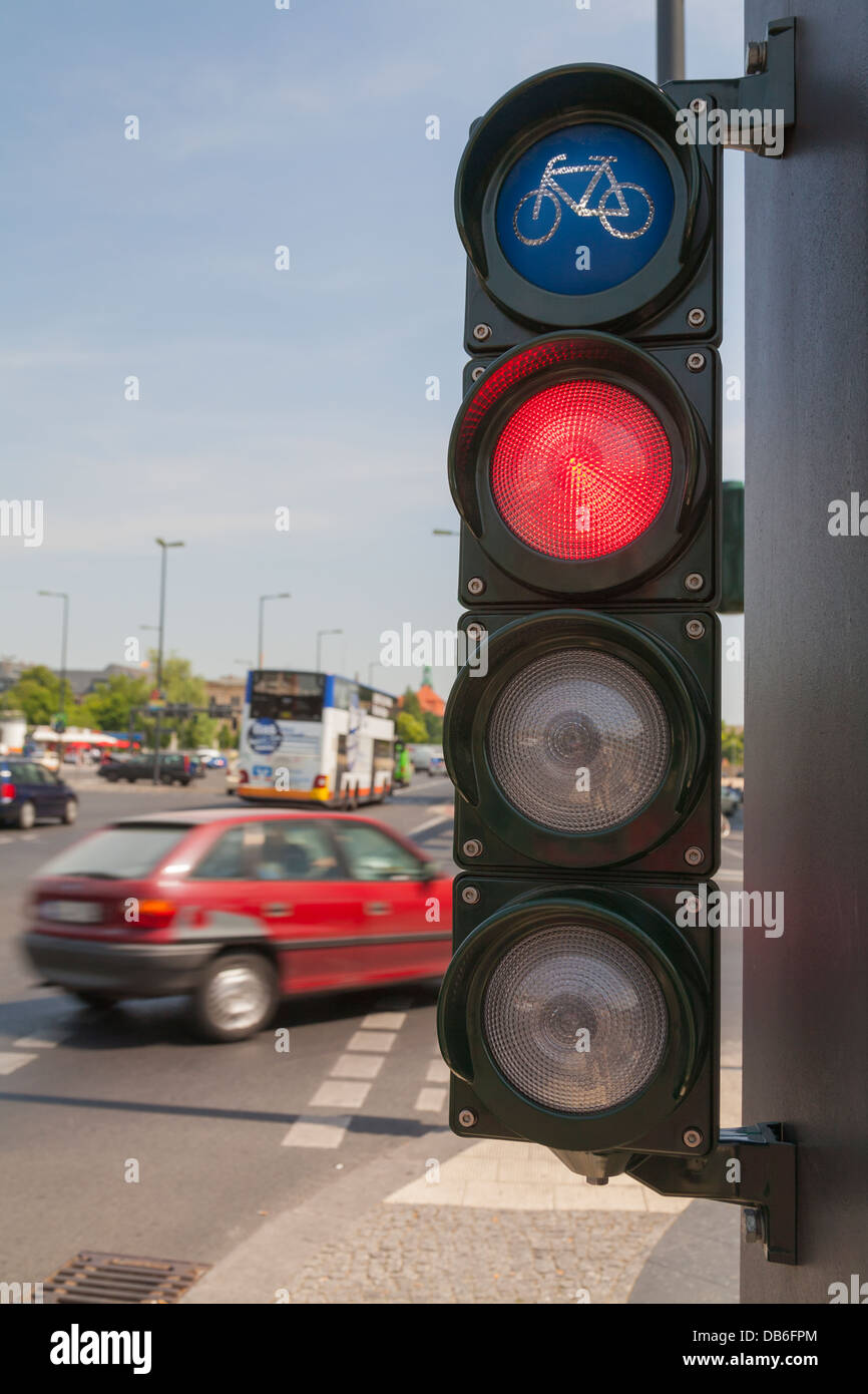 Traffic lights for cyclists, bicycle light turns red, a car cross the cycle way Stock Photo