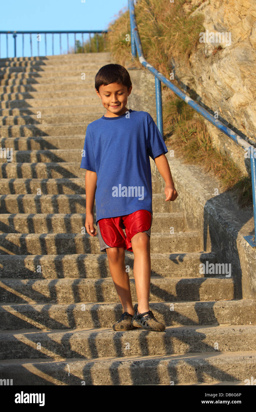 Young Hispanic boy smiles while coming down steps at an old harbor in England - Stock Image
