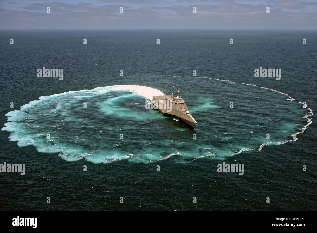 US Navy littoral combat ship USS Independence demonstrates its maneuvering capabilities by completing an 360-degree - Stock Image