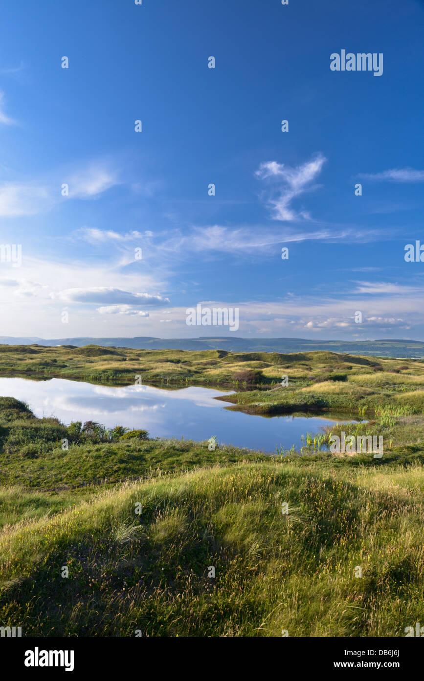 Dune slack pool and coastal dune system at Kenfig Nature Reserve - Stock Image
