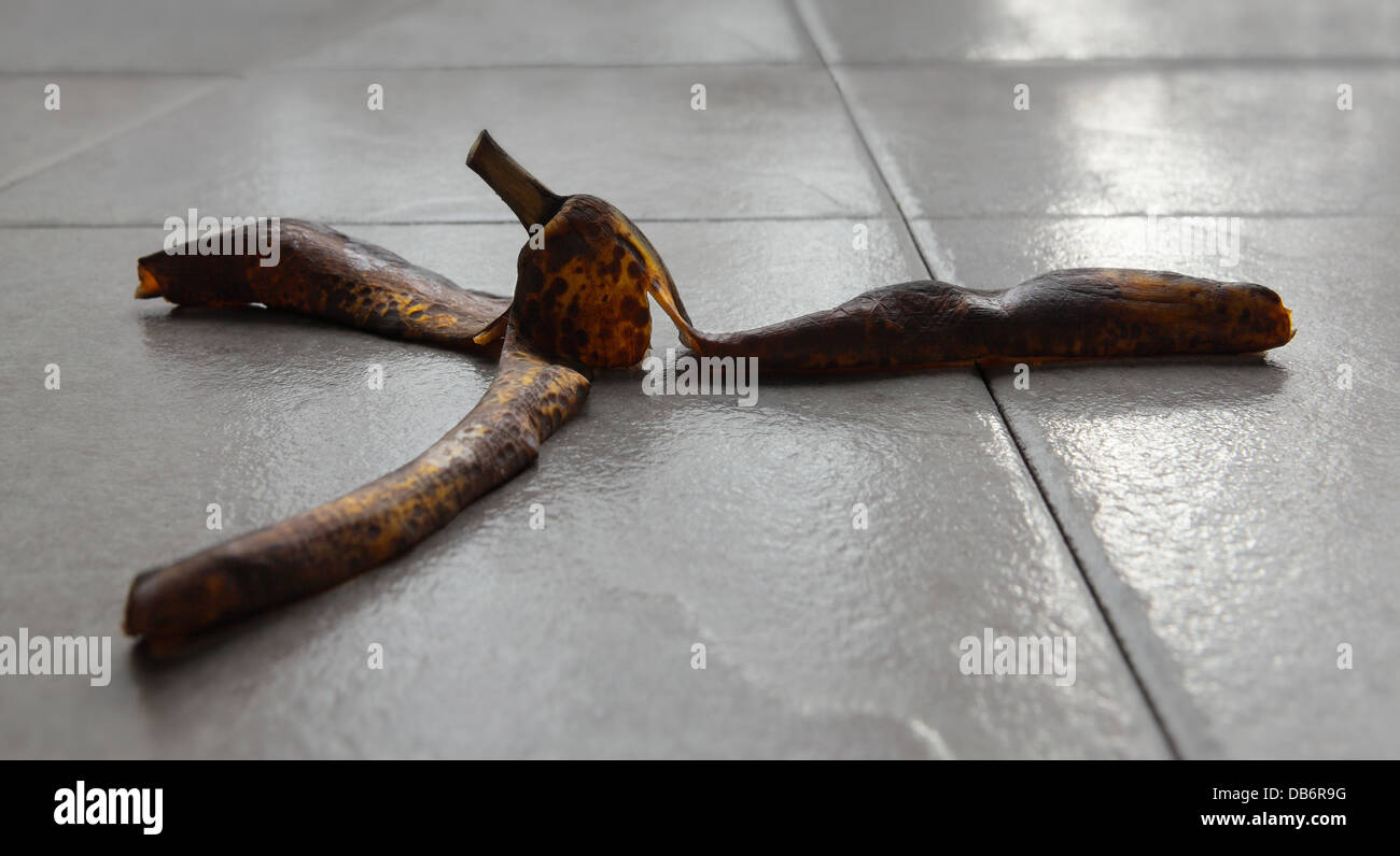 ripe bananas peels spread out on a ceramic floor - Stock Image