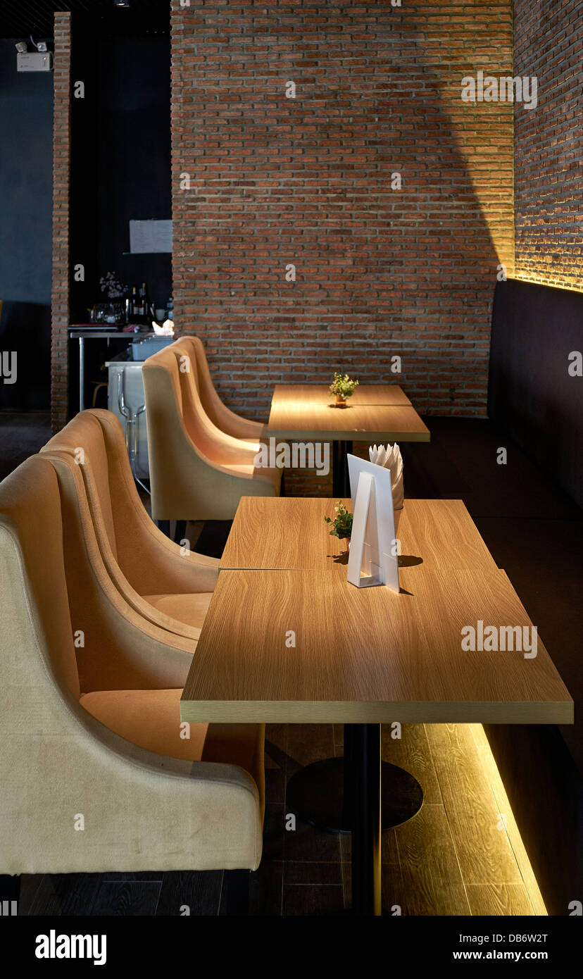 Modern boutique restaurant and wine bar dining area with soft furnishing and intimate lighting. - Stock Image