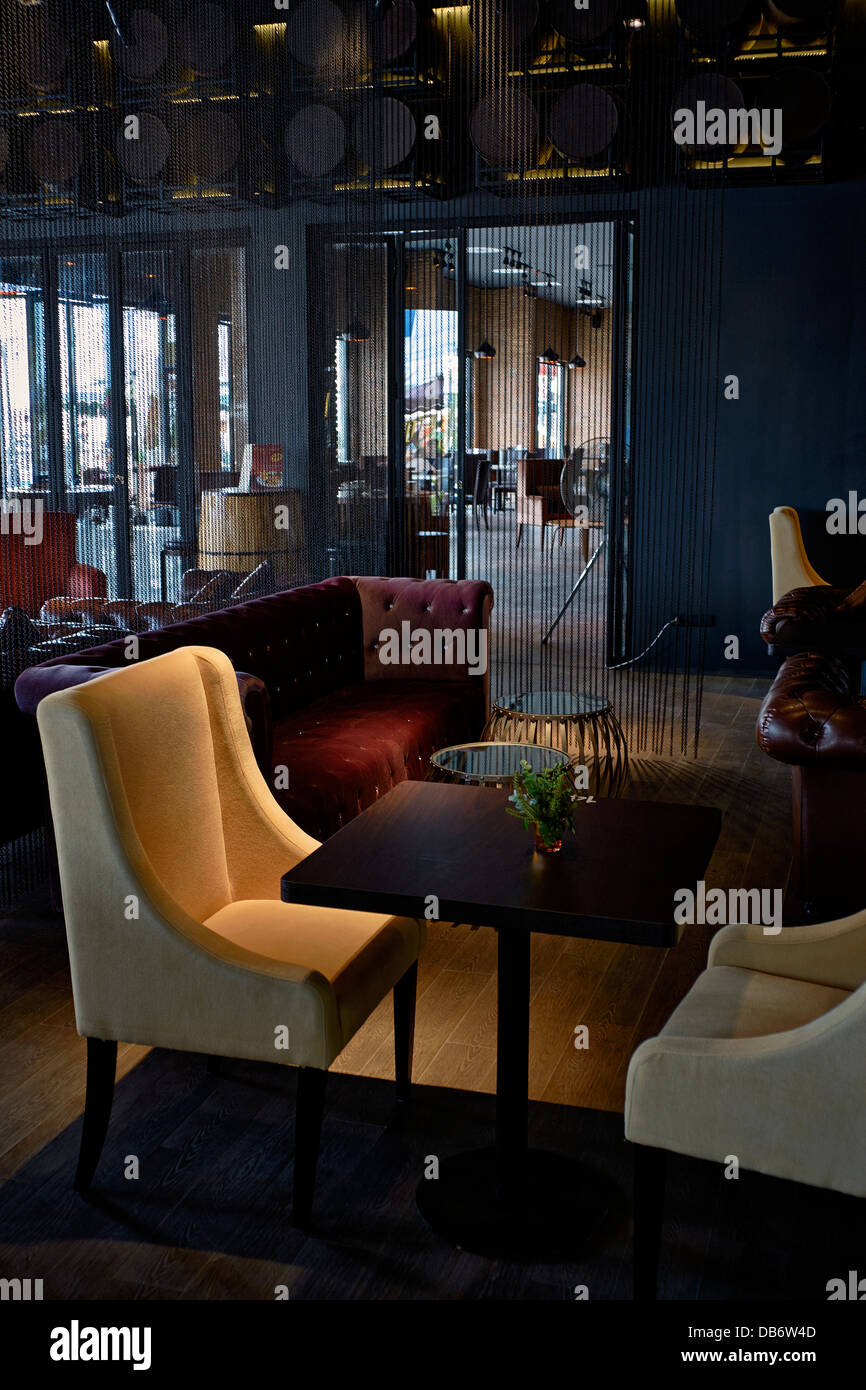 Interior of modern restaurant reception and lounge area with plush soft furnishing and soft lighting creating an - Stock Image