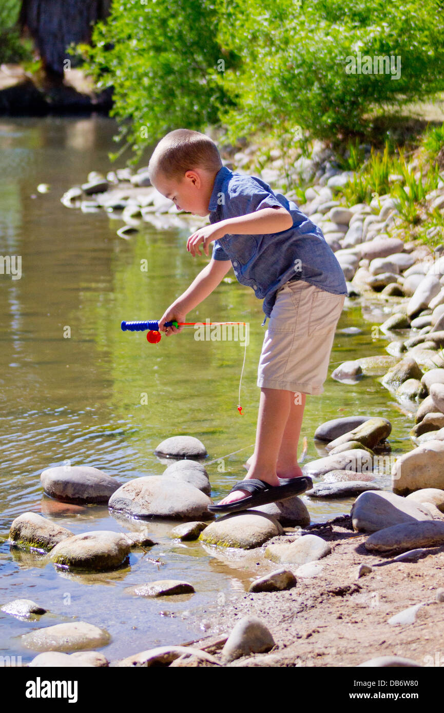 A fiver year old boy with autism goes 'fishing.' - Stock Image