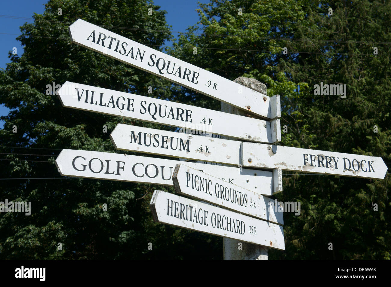 Signpost showing directions and distances to tourist attractions in Snug Cove on Bowen Island, BC, Canada Stock Photo