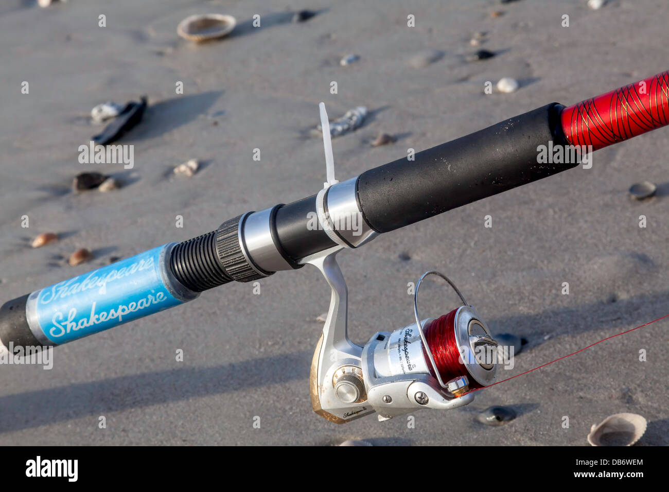 Shakespeare fishing rod and reel resting on sandy beach. - Stock Image