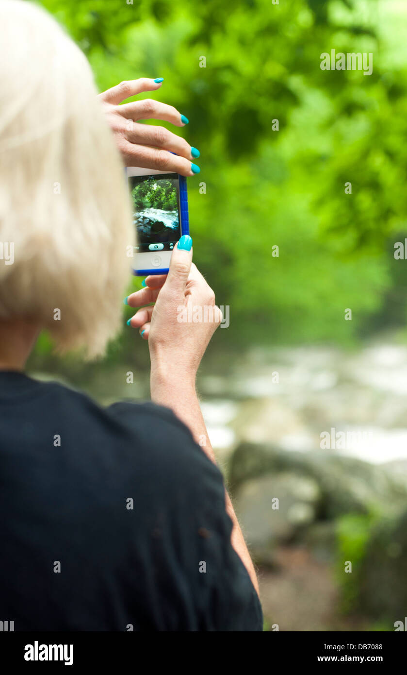 Lady photographing a landscape with cell phone camera, view from behind - Stock Image