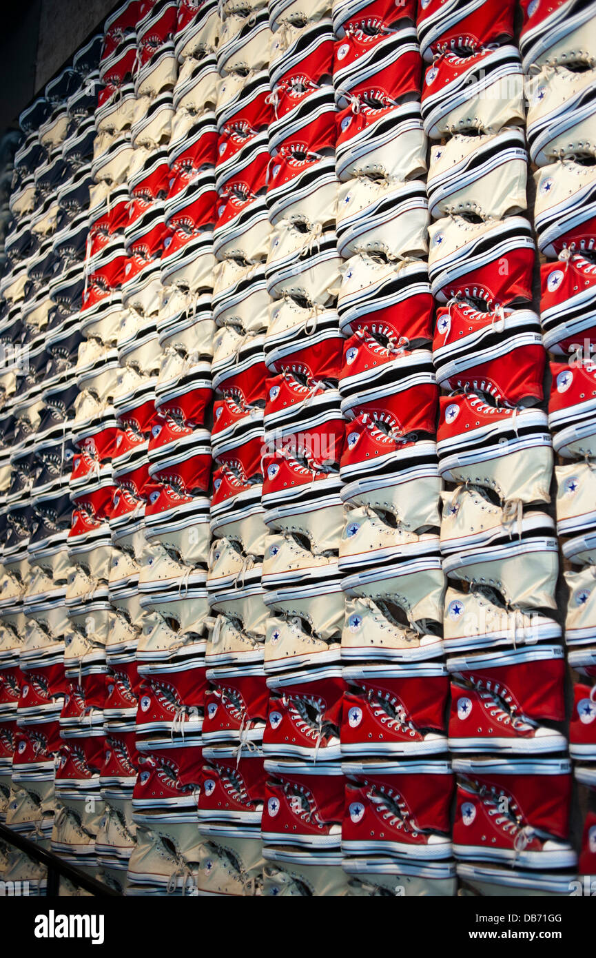 Converse Chuck Taylor All Stars tennis shoes on the wall at the Converse Shoe store in New York City - Stock Image