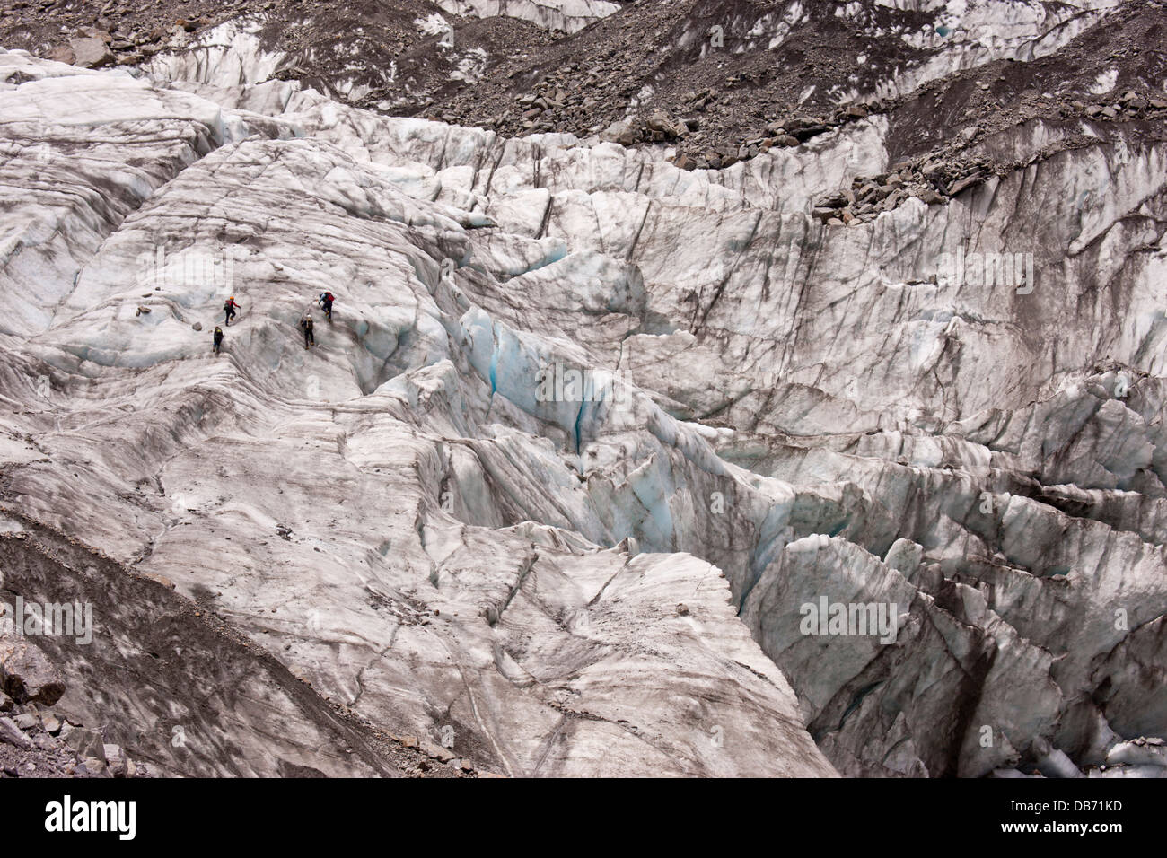 South Pacific, New Zealand, South Island. Hikers climbing on the icy snow of Fox Glacier with a guide. - Stock Image