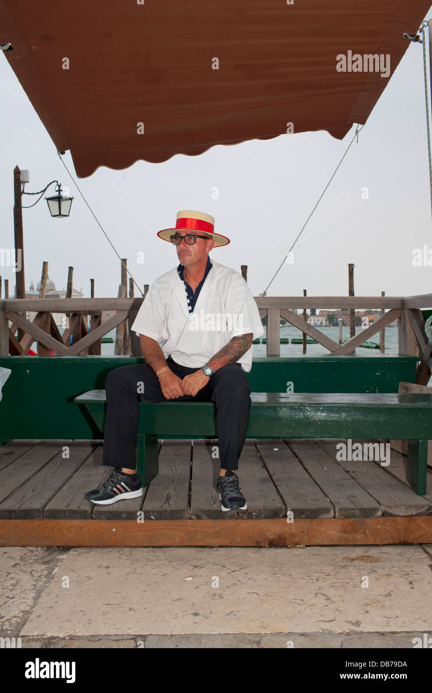 A gondola wearing glasses and a straw boater with a red ribbon waits for customers. - Stock Image
