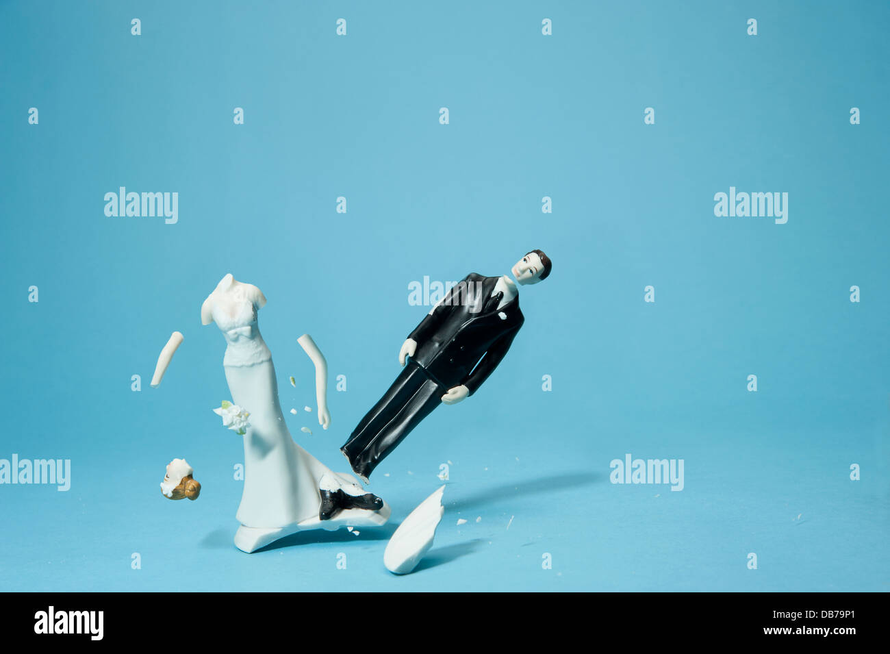 Bride and groom cake topper smashing apart - Stock Image