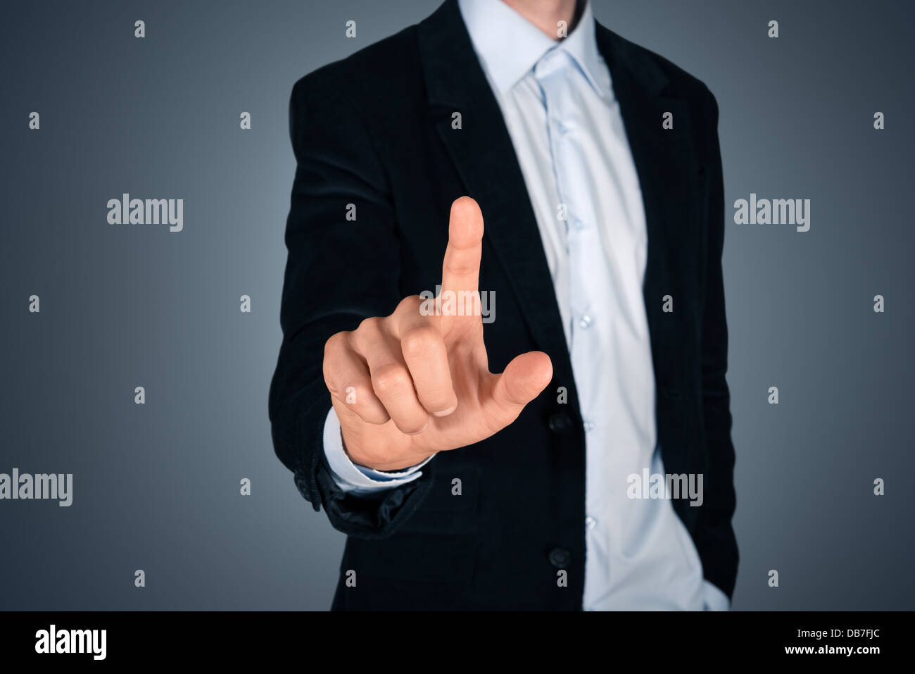 Portrait of handsome businessman touching a blank invisible screen. Touch screen concept image. Isolated on dark - Stock Image