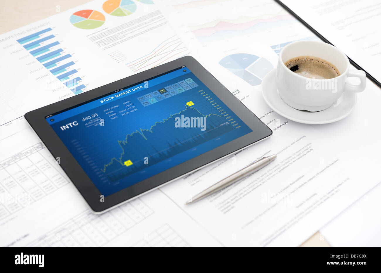 Modern digital tablet with stock market data application on a desk with some papers and documents, pen and a cup - Stock Image