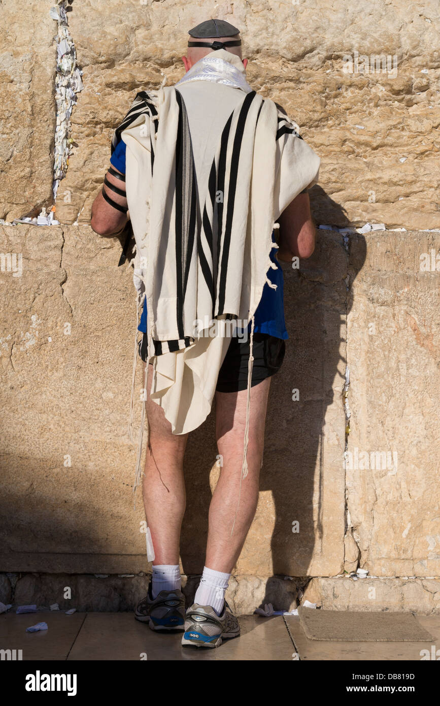 Jew in shorts and prayer shawl praying at the Western Wall. Jerusalem Old City. Israel. - Stock Image