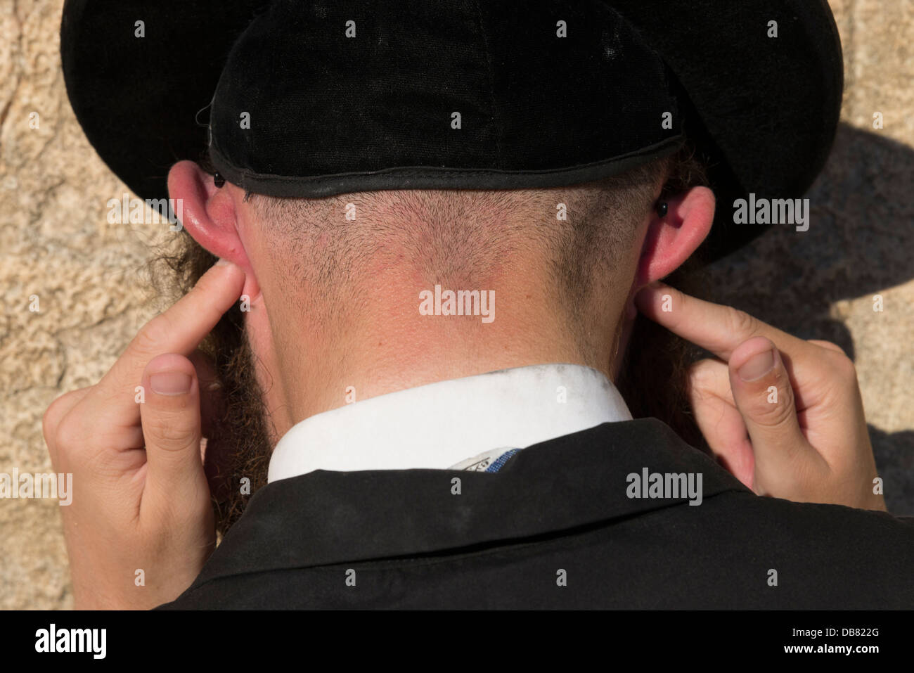 Portrait of an Orthodox Jew praying while blocking his ears. Western Wall. Jerusalem Old City. Israel. - Stock Image