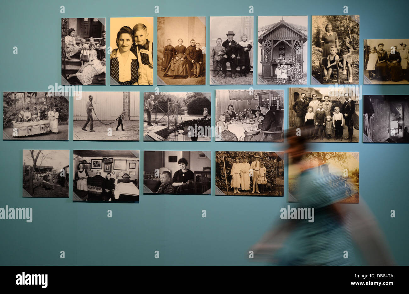A man walks past a photo wall at the exhibition 'Childhood pictures - Everyday photography in Brandenburg since - Stock Image
