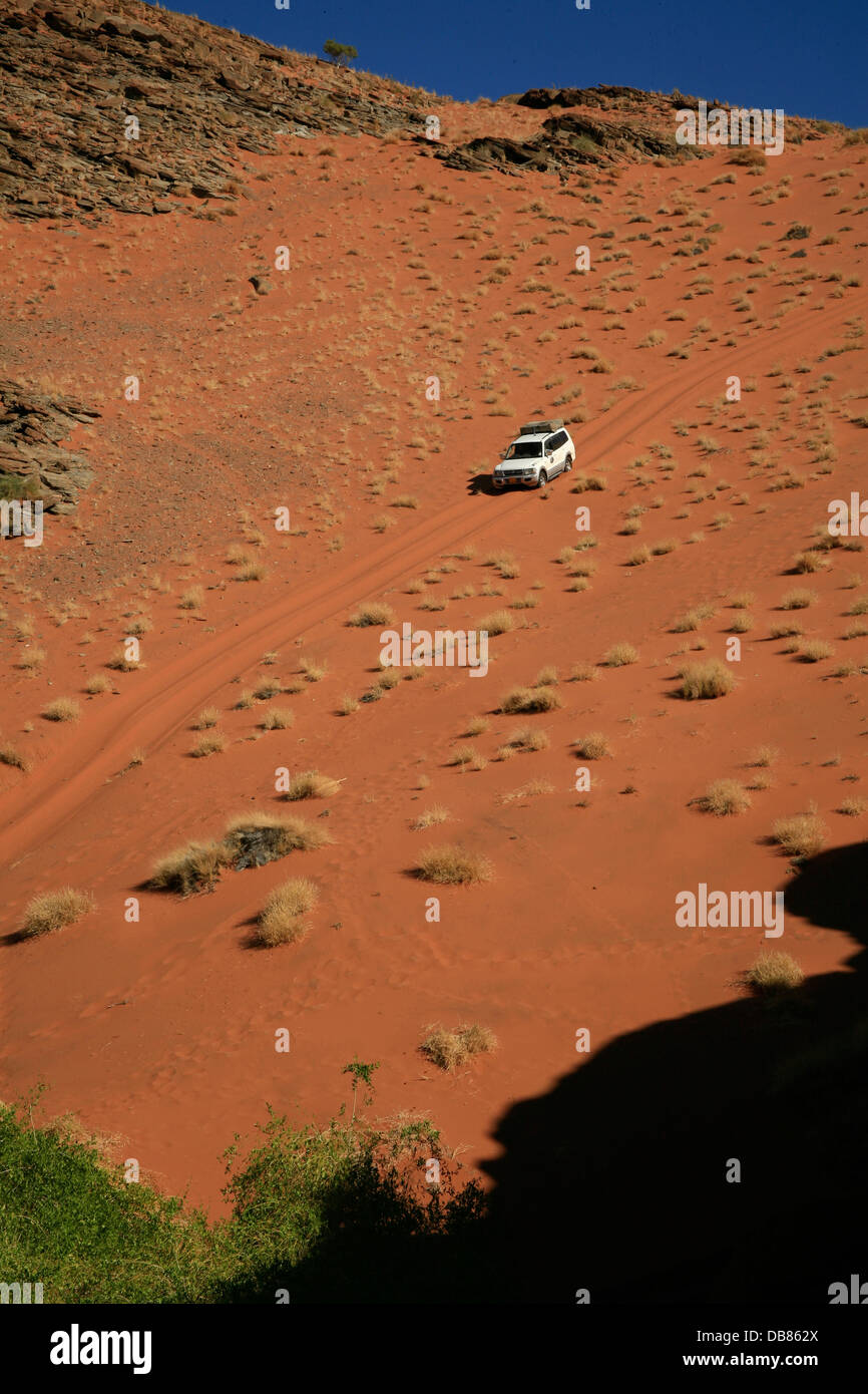 offroad vehicle on a big sand dune in the Namib Desert, Namibia - Stock Image